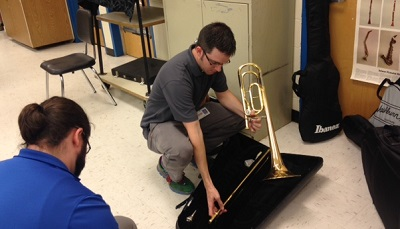Music teachers at Albemarle Road Middle School inspect donated instruments
