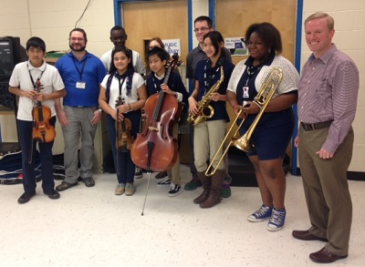 Music teachers and Symphony staff join students holding donated instruments